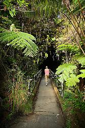 Woman visitor walking into Thurston Lava Tube ( Nahuku ), Hawaii Volcanoes National Park, Kilauea, Big Island, Hawaii