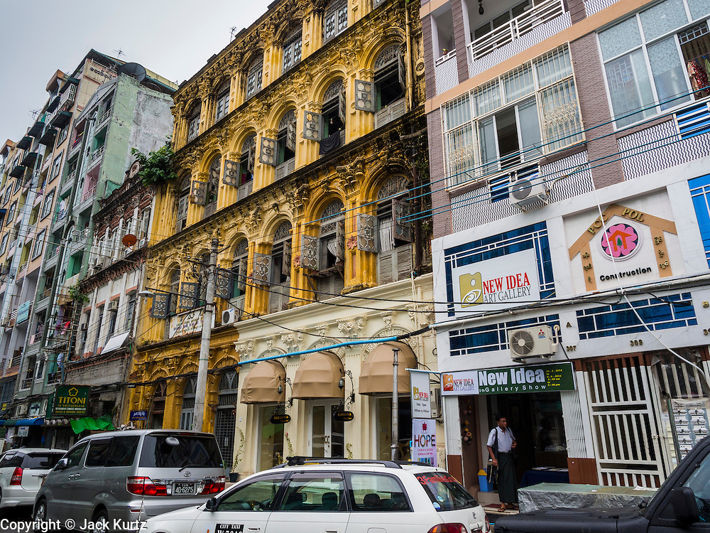 08 JUNE 2014 - YANGON, MYANMAR: A colonial building in disrepair nestled between two newer buildings on Bo Sun Pet (also spelled So Soon Pat) Street in Yangon. Yangon has the highest concentration of colonial style buildings still standing in Asia. Efforts are being made to preserve the buildings but many are in poor condition and not salvageable.    PHOTO BY JACK KURTZ