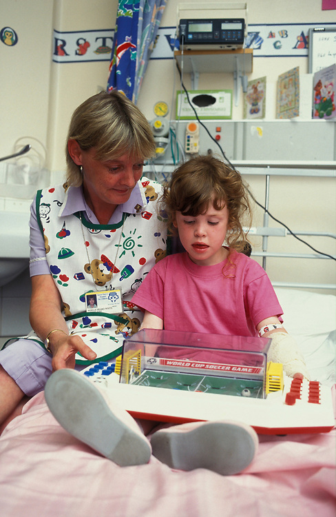 Nurse entertaining young child in Hospital ward,