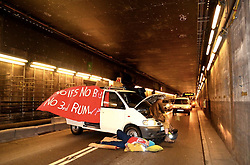 © Licensed to London News Pictures. 26/11/2015. London, UK. Activists block the tunnel attaching themselves to a vehicle across both lanes of the tunnel. A group of Airport expansion activists cause traffic chaos by blocking off the inbound tunnel of Heathrow airport in London to protest against airport expansion.  Photo credit: /LNP