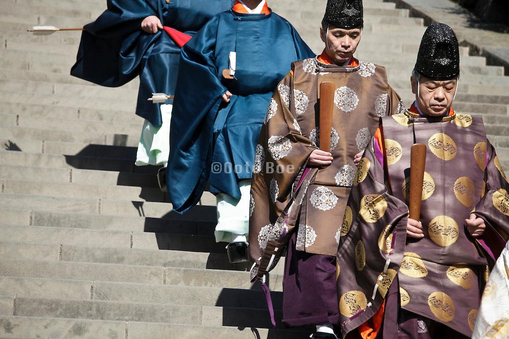 shinto priests walking down the stairs at the Tsurugaoka Hachimangu shinto shrine in Kamakura Japan