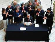 May 6, 2013 -Atlanta: Gov. Nathan Deal holds the two ethics bills he signed inside the Georgia State Capitol while surrounded by legislators on Monday, May 6, 2013.  House Bill 142 sets the first limit on gifts that can be given to legislators. The $75 maximum is for each expenditure. The second, House Bill 143, requires more transparency in regard to campaign fund-raising and spending during certain local races, and it ensures that the public knows about any campaign donations given to members of the General Assembly leading up to the start of the legislative session.  Deal made the passage of some sort of lobbying rules a legislative priority, even threatening a special session if the two GOP-controlled chambers couldn't pass a version by the end of the 40-day session.  JCRAWFORD@AJC.COM
