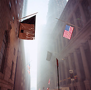 """Wall Street, Manhattan.Patriotic Americana - After 9/11.American flag hanging in a smoke-filled Wall Street..In the week after the September 11th attacks, America sought to express their anger and patriotic unity. On the Monday following the attacks, Wall Street sprang back into life and its disrupted workers returned to their dusty offices. Meanwhile, above their heads, flags hung defiantly from the financial institutions amid a blue, dusty haze. New York City. """"Star Spangled Banners."""" - From the American national anthem.."""