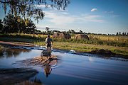2015/03/03 – Monte Maiz, Argentina: A man rides a tricycle on a path now-a-days covered with water. Floods are really common nowadays in the region, because the soil can't absorb much water since pestifies make it harder and less absorvent. Another reason is that soy needs less water than other crops, so the water under the soil its just a mere 30cm from the surface making floods common when rain falls. (Eduardo Leal)