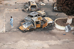 © under license to London News Pictures. 24/02/2011. A man walks by burnt out cars at the Army Compound in Benghazi, Libya. Photo credit should read Michael Graae/London News Pictures