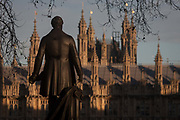 The statue of Sir Robert Peel and the British Houses of Parliament, on 17th January 2017, in Parliament Square, London England. The Elizabeth Tower previously called the Clock Tower named in tribute to Queen Elizabeth II in her Diamond Jubilee year – was raised as a part of Charles Barrys design for a new palace, after the old Palace of Westminster was largely destroyed by fire on the night of 16 October 1834. The new Parliament was built in a Neo-gothic style, completed in 1858 and is one of the most prominent symbols of both London and England. Sir Robert Peel, was a British statesman and member of the Conservative Party, served twice as Prime Minister of the United Kingdom and twice as Home Secretary. He created the modern police force and officers known as bobbies and peelers.