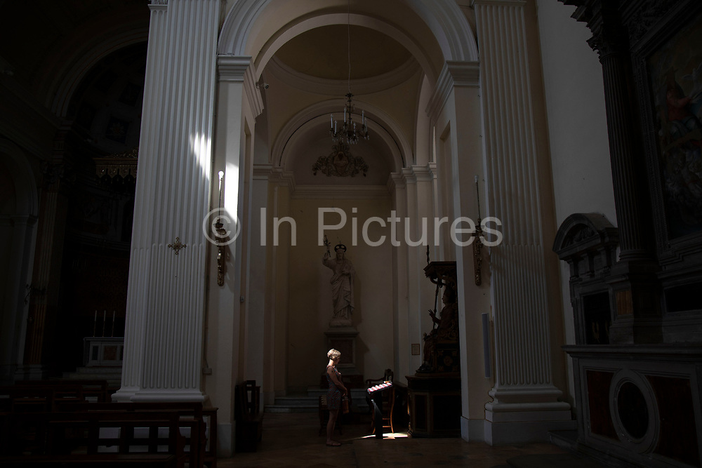 Woman beside candles in Saint Emiliano church in Trevi, Umbria, Italy. Trevi is an ancient town and comune on the lower flank of Monte Serano. The Duomo of Sant Emiliano is a Romanesque building with a carved door and an apse with carved corbels, the interior of which was significantly reworked in the 18th century.
