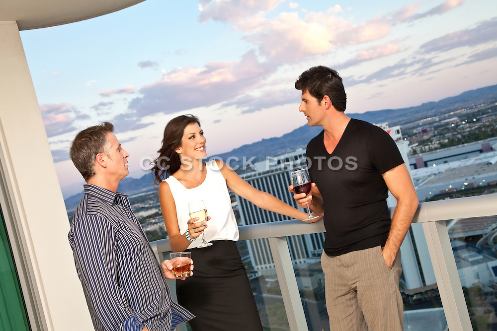 Friends Having cocktails On A Balcony After Work