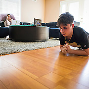 Spencer takes his virtual Physical Education class while Erin works from the couch after suffering a painful pinched-nerve overnight that limited her ability to move.