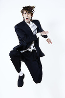 studio shot portrait of a young funny expressive thin and tall man on isolated background jumping