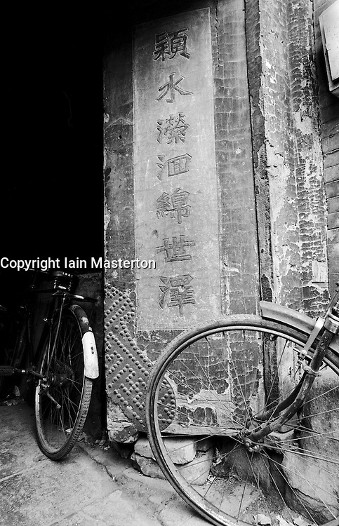 Bicycles parked outside a house with very old doors in a Beijing hutong