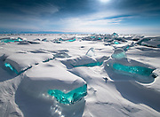 "Incredible Turquoise Ice Gleams Like Gemstones On Lake Baikal<br /> <br /> Landscape photographer Alexey Trofimov, who lives in Siberia, took these incredible pictures of the unusual phenomenon. Trofimov describes Lake Baikal itself as ""the pearl of our planet."" Perhaps, then, the extraordinary blue-colored ice formations are its accompanying sapphires.<br /> Lake Baikal is indeed remarkable, even without these striking icy marvels. Located in southeastern Siberia, the over 7.78 million-acre expanse of water is notable for being Earth's most ancient lake, dating back as it does some 25 million years. The bottom of this gigantic basin, meanwhile, lies 3,892 feet below sea level. However, the distance from the water's surface to its nethermost-recorded point measures an amazing 5,387 feet. Baikal is, in short, the deepest lake on the planet.<br /> <br /> Moreover, the lake's surroundings are exceptionally varied. Near to the huge body of water ""there are,"" as Trofimov tells us, ""high mountain ranges, impassable taiga, sandy beaches [and] wild steppes."" The weather is also fickle, with Baikal often bathed in sunshine but adjacent landforms or even other parts of the lake prone to experiencing very different conditions such as storms. Trofimov suggests that this contributes to the place being ""harsh and dangerous as [well as] beautiful.""<br /> <br /> Given the intriguing array of environmental spectacles in, over and around the lake, it seems a fitting place to find a captivating wonder like the turquoise ice formations pictured here. The brightly hued ice reveals itself around March each year, and many people make their way to the area in order to witness its beauty at this time.<br /> <br /> These unique frozen formations are in fact called ice hummocks. The knolls are created in part by pressure that develops gradually and unevenly in the layer of ice that covers Lake Baikal in winter. The physical make-up and temperature of the ice sheet then also become imbalanced, and hence the hummocks form an"