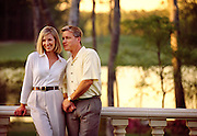 A couple enjoys a sunset from the balcony of a luxurious Country Club & Golf Resort