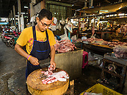 14 DECEMBER 2015 - BANGKOK, THAILAND:  A butcher in Bang Chak Market. The market closes permanently on Dec 31, 2015. The Bang Chak Market serves the community around Sois 91-97 on Sukhumvit Road in the Bangkok suburbs. About half of the market has been torn down. Bangkok city authorities put up notices in late November that the market would be closed by January 1, 2016 and redevelopment would start shortly after that. Market vendors said condominiums are being built on the land.      PHOTO BY JACK KURTZ