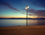 The last moments of street lighting illuminates the pavement and road as dawn breaks over the shoreline on the untidy and empty seafront in Nea Makri, a coastal town near Athens on the Marathon road. This town is the original route that the Athenian messenger Pheidippides ran in 490BC to deliver news of the Greek victory over Persia in the Battle of (Marathonas) Marathon. Nowadays, this is a rather unattractive town with few echoes of Greece's ancient glories although the 29th modern Olympic circus came home in 2004. The modern games share many characteristics with its ancient counterpart. Corruption, politics and cheating interfered then as it does now and the 2004 Athens Olympiad echoed both what was great and horrid about the past.