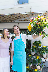 Salesman with customer holding bunch of flowers, smiling