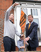 © Licensed to London News Pictures. 26/04/2015. Sutton, UK.  NICK CLEGG, PAUL BURSTOW hammer in a stake board at the home the Bourne family who live on Orchard Road.  leaflets Orchard Road in Sutton.  Deputy Prime Minister and Leader of the Liberal Democrats Nick Clegg makes a speech today, 26th April 215 in Sutton, to local Liberal Democrats in support of the candidate for Sutton and Cheam, Paul Burstow. Nick Clegg and Paul Burstow also joined local campaigners to deliver leaflets on a nearby street, and put up a Liberal Democrat stakeboard.. Photo credit : Stephen Simpson/LNP