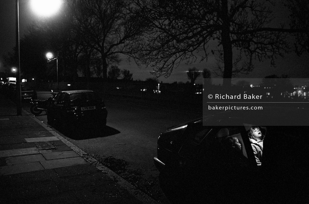 "Late at night in a South London street, two young children remain fast asleep in the back of their parents' car. It is a dark despite pools of light falling from street lighting that throw heavy shadows beneath other vehicles. The silhouettes of large ash trees can be seen against the city skyline. The interior lights in the car are switched on to reveal the sleeping childrens' faces. An older girl has her mouth wide open while her younger brother is seen in profile but both are peacefully unaware that they have arrived home after a long drive fro the countryside to the inner-city. From a personal documentary project entitled ""Next of Kin"" about the photographer's two children's early years spent in parallel universes. Model released."