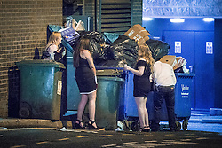 © Licensed to London News Pictures . 01/01/2016 . Manchester , UK . Men and women urinate amongst bins and rubbish . Revellers in Manchester on a New Year night out at the clubs around the city centre's Printworks venue . Photo credit : Joel Goodman/LNP