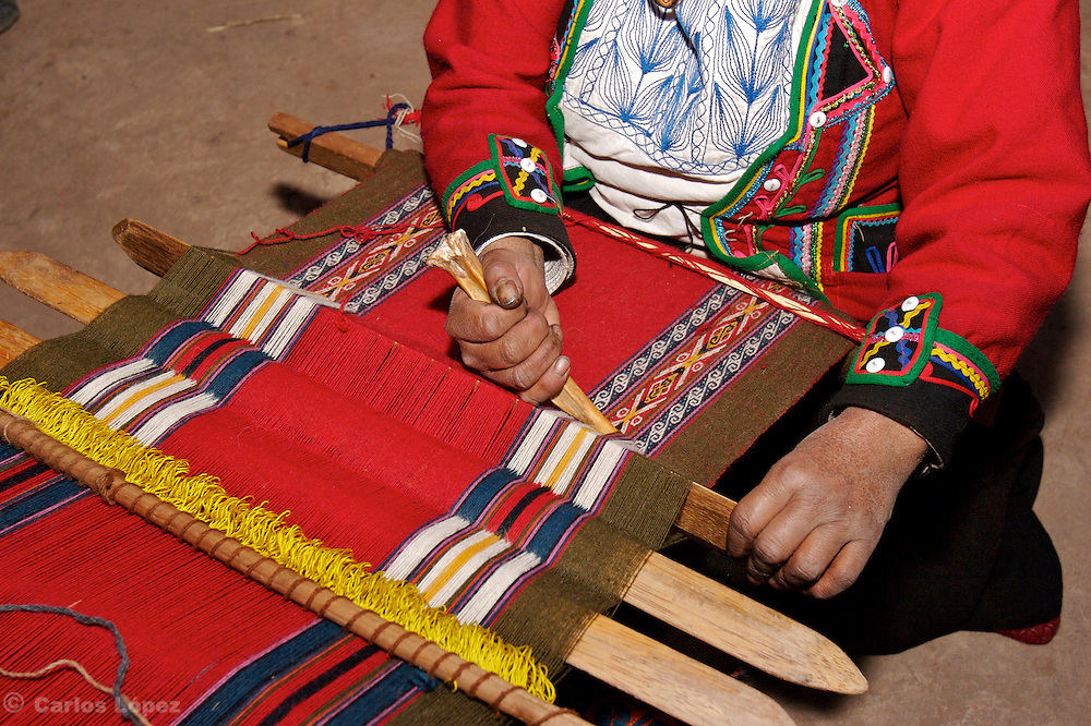A WOMAN IS MAKING CLOTHES IN THE TRADITIONAL WAY IN THE TOWN OF CHINCHEROS , CUSCO, PERU. SHE IS USING THE BONE OF A SHEEP.