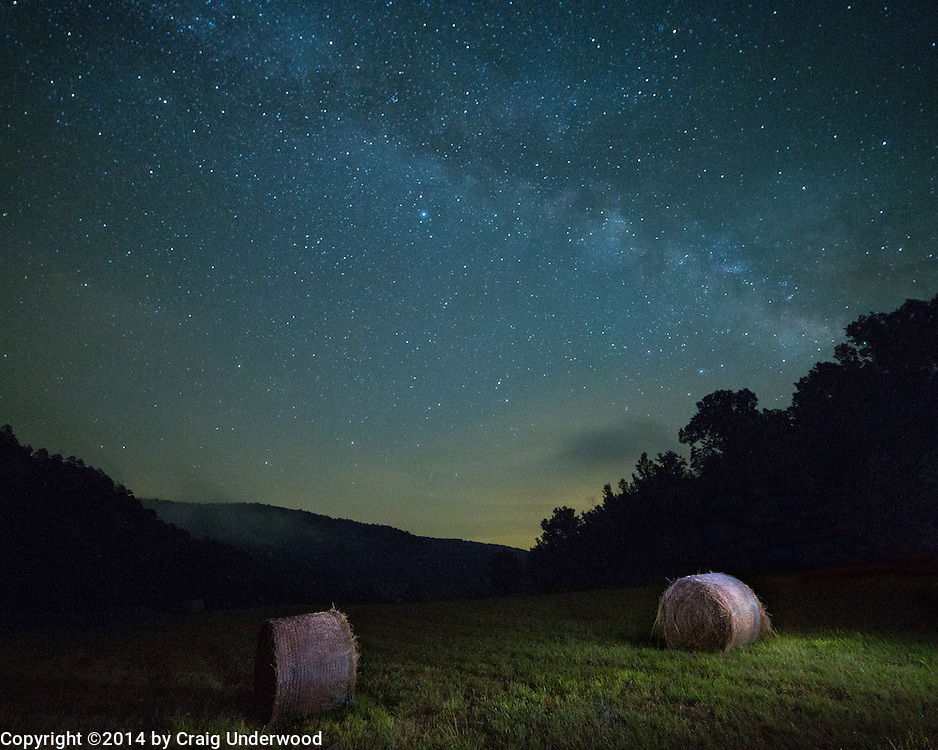 """This was taken in the Buffalo River National Park back in 2014 around 12:30 in the morning.  I was up late trying to capture some images of the Milky Way when I noticed these two bales in the field.  Images of stars require a time exposure of approximately 20 seconds.  I used this time to take out my flashlight and illuminate the hay bales (a technique known as """"painting"""" light on a subject)"""