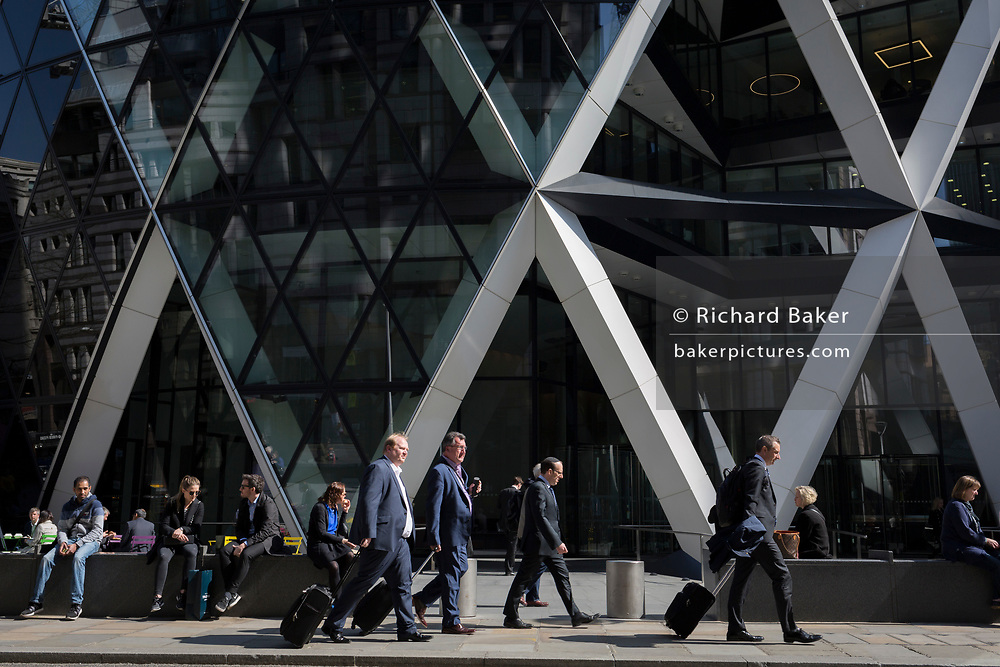 Business people walk beneath the architectural struts of the Swiss Re at 30 St. Mary Axe in the City of London, the capital's financial district also known as the Square Mile, on 6th April 2017, in London, England.