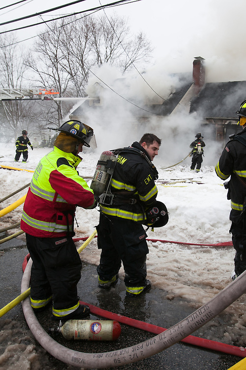 Hingham, MA 02/11/2013.A Hingham firefighter gets a new air bottle while fighting work a 3 alarm house fire at 276 East St. in Hingham on Monday, February 11..Alex Jones / www.alexjonesphoto.com