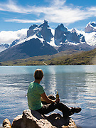 A woman sits on a rock and enjoys the view of Cuerno Principal over Lago Pehoe, Torres del Paine National Park, Chile.
