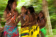 Young Embera girls dancing and playing music. Churuco, Darien Province, Panama.