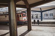 Sarajevo, Bosnia and Herzegovina - October 5, 2013: Two men walk across the tracks at the train station in Sarajevo.