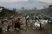 An Afghan girl walks inside a snow-covered graveyard in Kabul, Afghanistan, Sunday, Feb. 11, 2007. Heavy rain and snow falls in Kabul area for three consecutive days resulted in partial floods collapse of walls, and muddy roads.