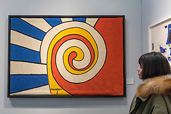 "© Licensed to London News Pictures. 16/01/2018. LONDON, UK. A visitor views ""Three Spirals"" by Alexander Calder. Preview day of the 30th anniversary of the London Art Fair.  The fair launches the international art calendar with modern and contemporary art from leading galleries around the world and is taking place at the Business Design Centre, Islington from 17 to 21 January 2018.   Photo credit: Stephen Chung/LNP"