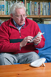 Older man using a large button telephone to make dialling a phone number easier to see when making a phone call,