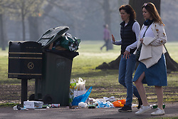 © Licensed to London News Pictures. 31/03/2021. London, UK. Members of the public walk past an overflowing bin in Greenwich Park after hundreds of people visited the park to enjoy sunny weather and take advantage of new lockdown rules that allow groups of six to meet outside. Photo credit: George Cracknell Wright/LNP