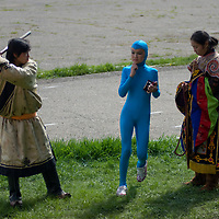 An acrobat runs through antics between Tibetan Buddhist Tsam dancers at the national Naadam festival in Ulaanbaatar, Mongolia.