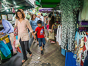 22 AUGUST 2014 - BANGKOK, THAILAND:      People walk among clothing vendors on the sidewalks along Silom Road in Bangkok's Central Business District. The Thai military junta, formally called the National Council for Peace and Order (NCPO), has ordered street vendors off of the sidewalks in an effort to bring order to Bangkok's chaotic sidewalks. Vendors have complained that the new regulations are hurting them economically but largely complied with the military orders.      PHOTO BY JACK KURTZ