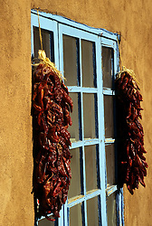 """North America, United States, New Mexico, Santa Fe, """"ristra"""" strands of dried chili peppers hanginng by window of adobe house"""