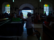 21 JANUARY 2018 - LEGAZPI, ALBAY, PHILIPPINES: A woman prays during Sunday mass at Our Lady of the Gate Parish in Legazpi. The church, built in 1773, was known by its Spanish name, Parroquia Nuestra Señora de la Porteria, before the American colonization of the Philippines.     PHOTO BY JACK KURTZ