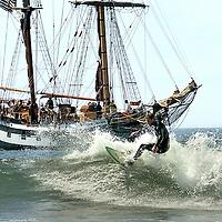 The tall ship Hawaiian Chieftan comes into the Santa Cruz, California harbor as a surfer grabs a ride at the harbor mouth.<br /> Photo by Shmuel Thaler <br /> shmuel_thaler@yahoo.com www.shmuelthaler.com