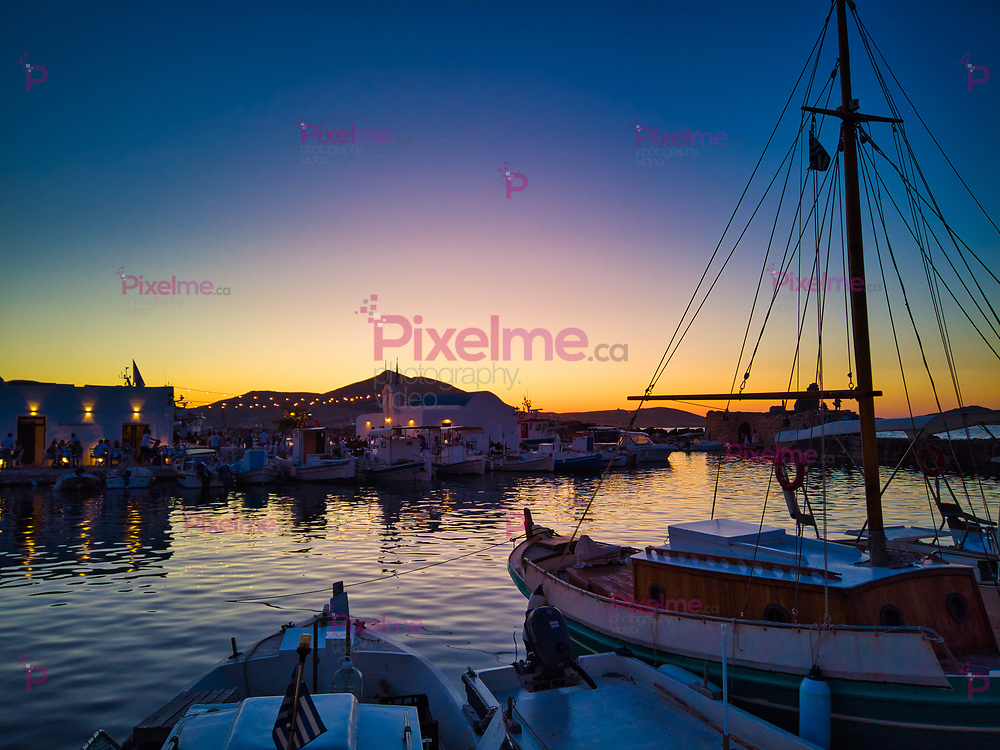 Picturesque view of tranquil old port with anchored sailboats in Naoussa Greece at dusk