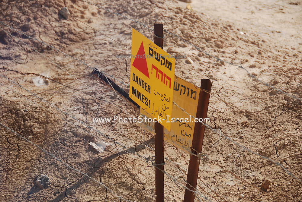 """Israel, Aravah, near the Jordanian border A mine field, a yellow warning sign in Hebrew Arabic and English """"Danger Mines"""""""