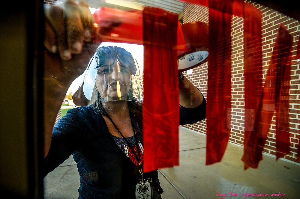 Violine Karam adds signage to polling place door. Voters line up to vote before polls open in the 2020 general election at Farmersville Elementary School in Bethlehem Township on November 3, 2020.