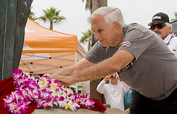 March 6, 2018 - FILE - Big-wave pioneer, surf innovator, mentor and historian George Downing has passed away at 87. Born and raised in Honolulu, Downing surfed Hawaii in the '40s on finless Hot Curls made out of redwood. He was a surfer responsible for many firsts in the sport, and in 1950 he produced the first surfboard with a removable fin. Eight years later he and a handful of other surfers rode 30 foot waves at Makaha, pushing the boundaries of what was believed to be possible at the time. Pictured: Aug. 05, 2011 - Huntington Beach, California, U.S. - GEORGE DOWNING places a lei at the base of the Duke Kahanamoko statue just prior to his induction into the 2011 Surfers Hall of Fame in front of Huntington Surf & Sport..(Credit Image: © Mark Rightmire/The Orange County Register/ZUMAPRESS.com)