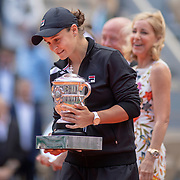 PARIS, FRANCE June 08.  Ashleigh Barty of Australia with the trophy heads to the podium presented by Chris Evert after after her victory against Marketa Vondrousova of the Czech Republic on Court Philippe-Chatrier during the Women's Singles Final match at the 2019 French Open Tennis Tournament at Roland Garros on June 8th 2019 in Paris, France. (Photo by Tim Clayton/Corbis via Getty Images)