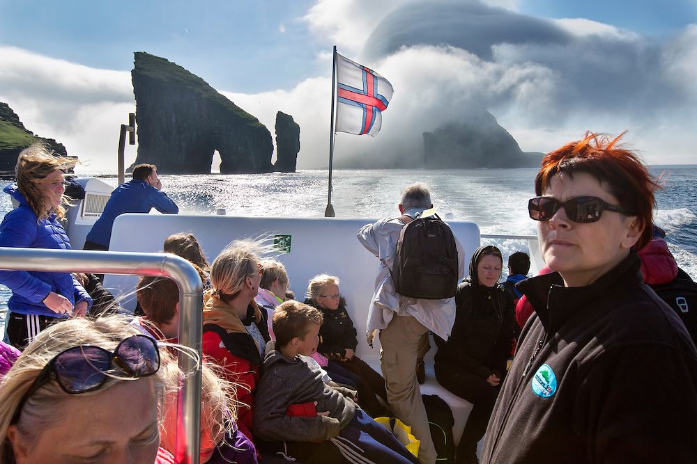 Tourists and Faroese locals ride the ferry from Mykines Island in the Faroe Islands, back to Sorvagur through the Sorvagsfjordur.  The Drangarnir rock arch (left) provides some stunning scenery for all who are watching, as does Tinholmur island which is covered in low lying clouds.<br /> <br /> Faroe Islands.