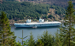 Glenmallan, Argyll and Bute, Scotland, UK. 18 March 2021.   On a rare visit to Scotland, the aircraft carrier HMS Queen Elizabeth berthed on the side of Long Loch at Glenmallan ahead of naval exercises which are part of the UK Carrier Strike Group 2021. Iain Masterton/Alamy Live News