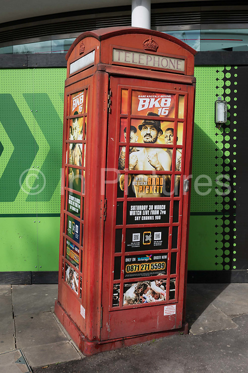 A classic phone box kiosk leans at an angle while advertising cage fighting, on 25th March 2019, in London, England.