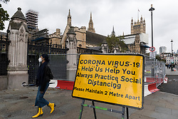 © Licensed to London News Pictures. 15/10/2020. LONDON, UK. A woman wearing a facemask and bright yellow boots walks by a coronavirus alert sign outside the Houses of Parliament in Westminster.  Currently, England alert level : Tier 1, Medium (the rule of six applies indoors and outdoors, pubs and restaurants shut at 10pm) applies, but to try to further control the coronavirus pandemic, the UK government has announced today that from Saturday the capital, as well as other regions in the UK, will move to the more stringent England alert level :Tier 2, High (no households mixing indoors, the rule of six applies outdoors, pubs and restaurants shut at 10pm).  Photo credit: Stephen Chung/LNP