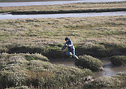 Boy jumping over salt marsh,  Street Orford Ness spit, Suffolk, England
