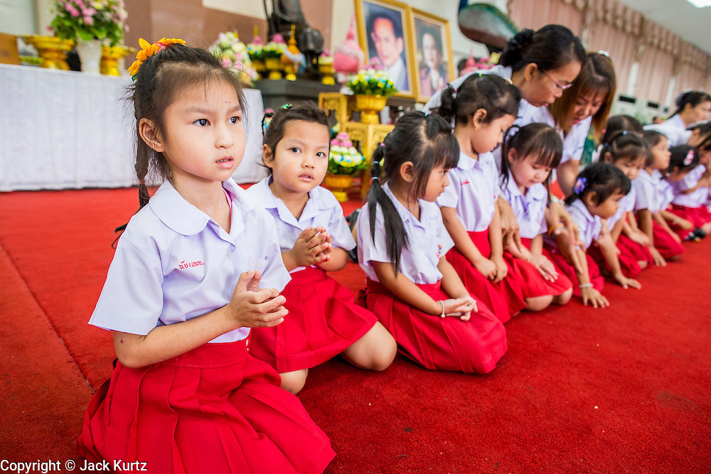 26 NOVEMBER 2012 - BANGKOK, THAILAND:  School children line up for photos in front of a portrait of the King of Thailand at Siriraj Hospital in Bangkok. Siriraj was the first hospital in Thailand and was founded by King Chulalongkorn in 1888. It is named after the king's 18-month old son, Prince Siriraj Kakuttaphan, who had died from dysentery a year before the opening of the hospital. It's reported to one of the best hospitals in Thailand and has been home to Bhumibol Adulyadej, the King of Thailand, since 2009, when he was hospitalized to treat several ailments. Since his hospitalization tens of thousands of people have come to pay respects and offer get well wishes. The King's 85th birthday is on Dec 5 and crowds at the hospital are growing as his birthday approaches. The King is much revered throughout Thailand and is seen as unifying force in the politically fractured country.       PHOTO BY JACK KURTZ